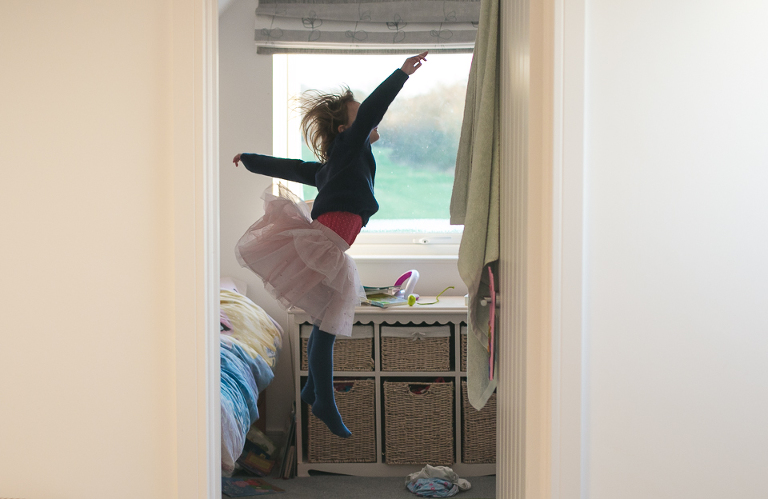 girl in skirt jumps off bed - Family Documentary Photography