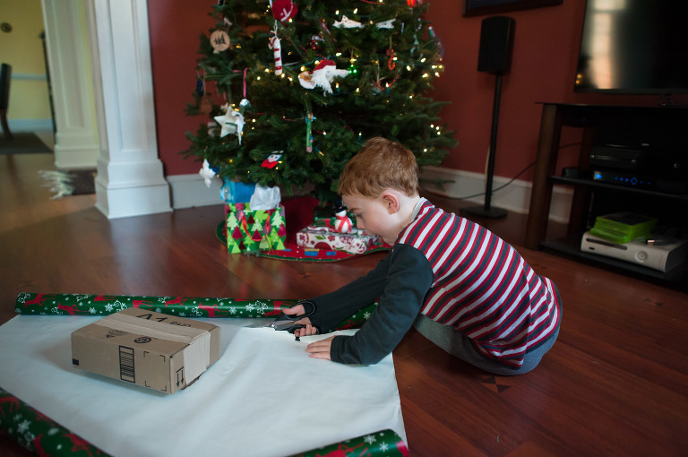 young boy wraps present - Family Documentary Photography