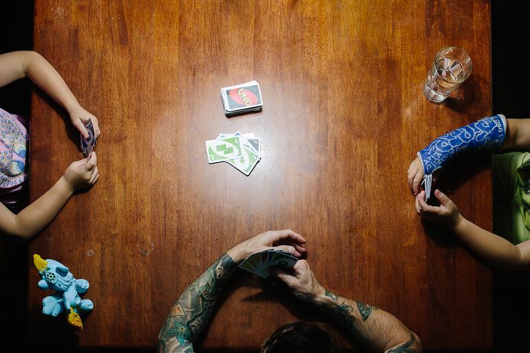 Family plays cards at kitchen table - Documentary Family Photography