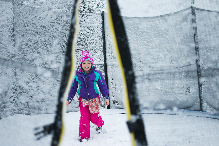 girl on snowy trampoline - Documentary Family Photography
