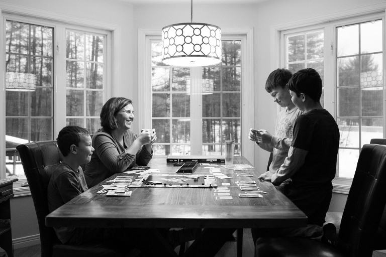 Family plays board game at table - Documentary Family Photography
