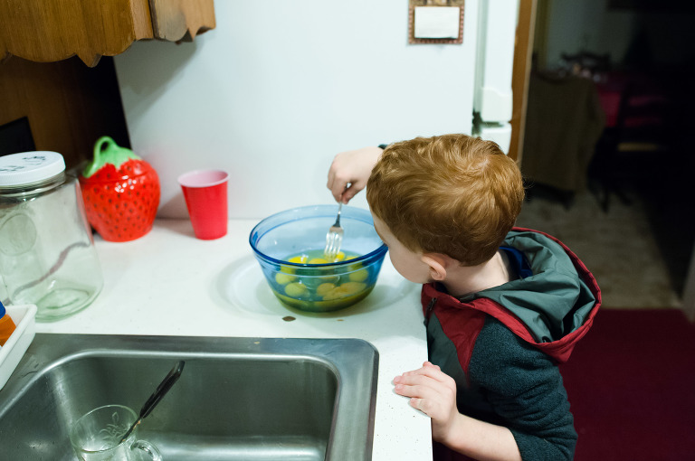 Boy stirs bowl of eggs - Documentary Family Photography