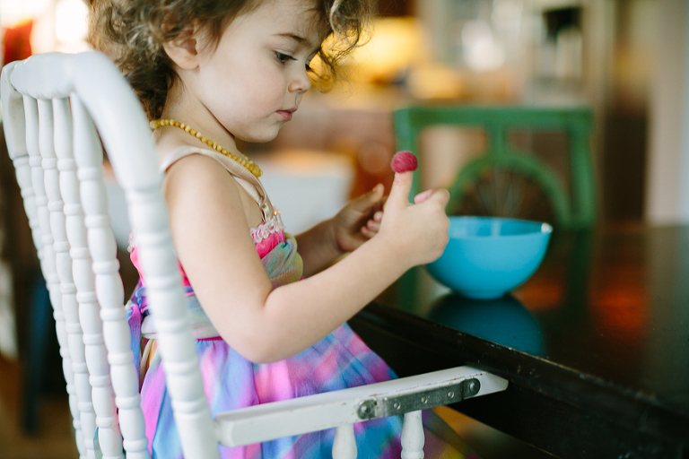 girl with raspberry on thumb - Documentary Family Photography