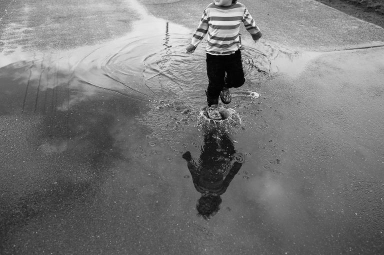 boy splashing in puddle - Documentary Family Photography