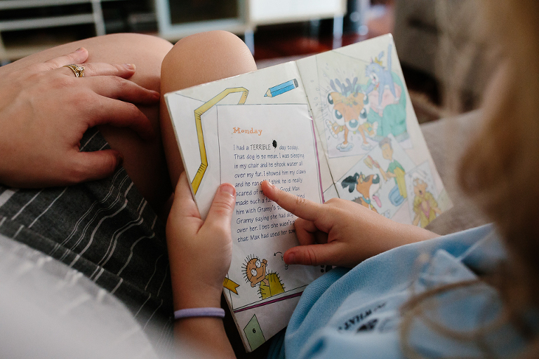 Child reading book next to parent - Documentary Family Photography