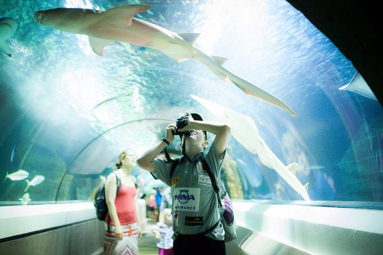boy watching sharks swim in aquarium - Documentary Family Photography