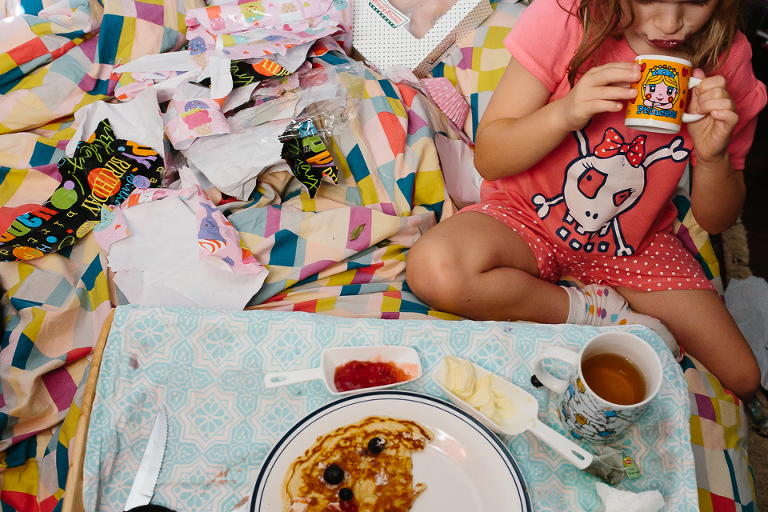 girl eats breakfast in bed - Documentary Family Photography