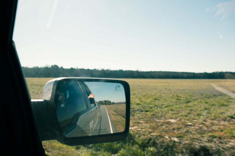 rear view mirror showing child's hand out window - Documentary Family Photography