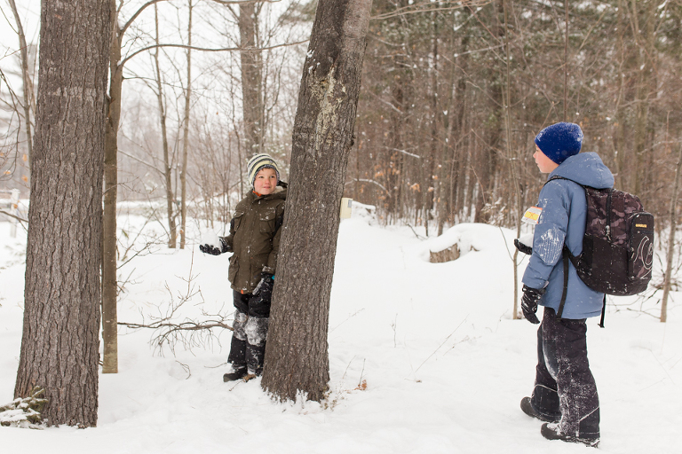 boy waiting behind tree with snowball - Documentary Family Photography