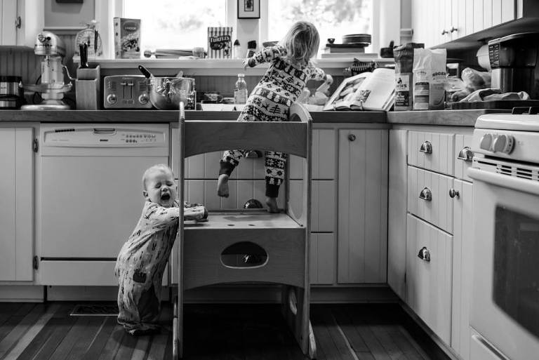 child at kitchen sink while baby cries at feet - Documentary Family Photography
