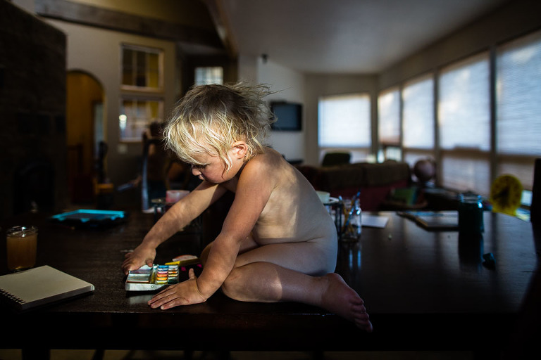 bare child with markers on top of table