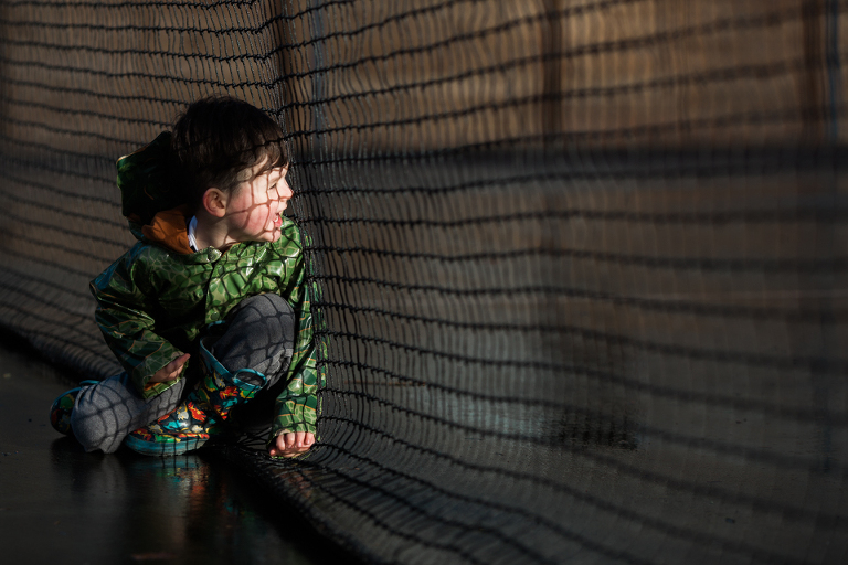 boy looking through netting - Documentary Family Photography
