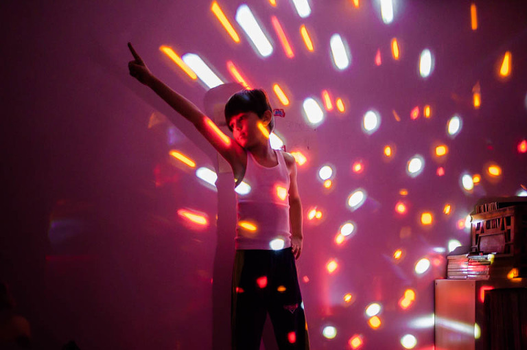 boy in disco pose with lights - Documentary Family Photography