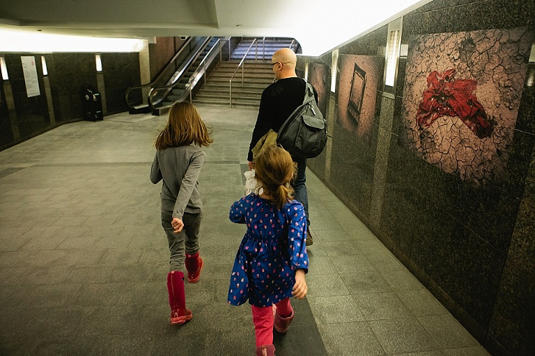 girls following father through train station - Documentary Family Photography