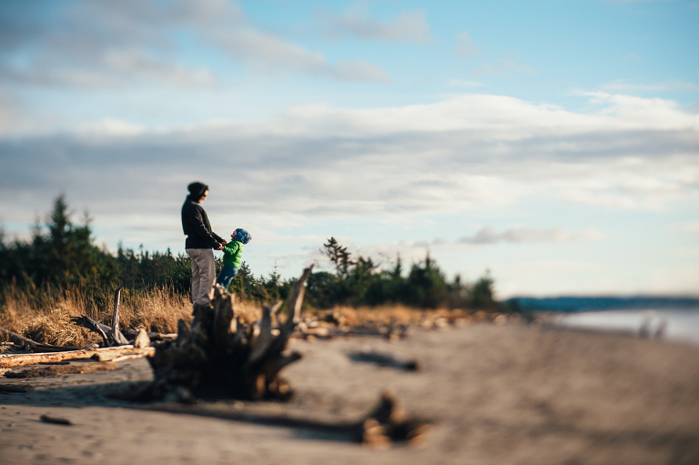 father and son climb driftwood at the beach - Documentary Family Photography