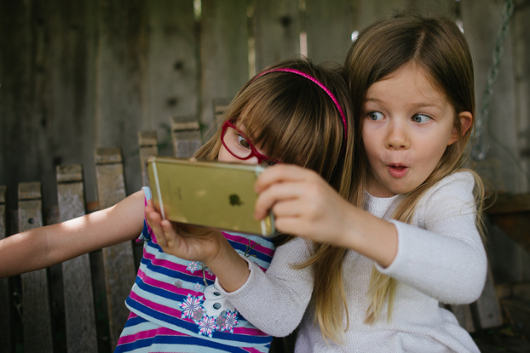 girls play on smartphone - Documentary Family Photography