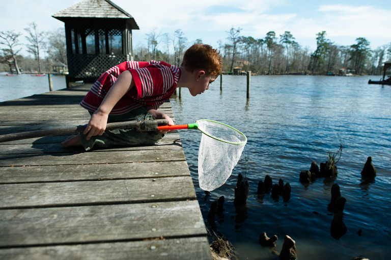 boy leans over dock with small fishing net - Documentary Family Photography