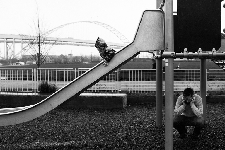 boy going down slide while dad talks on phone, documentary family photography