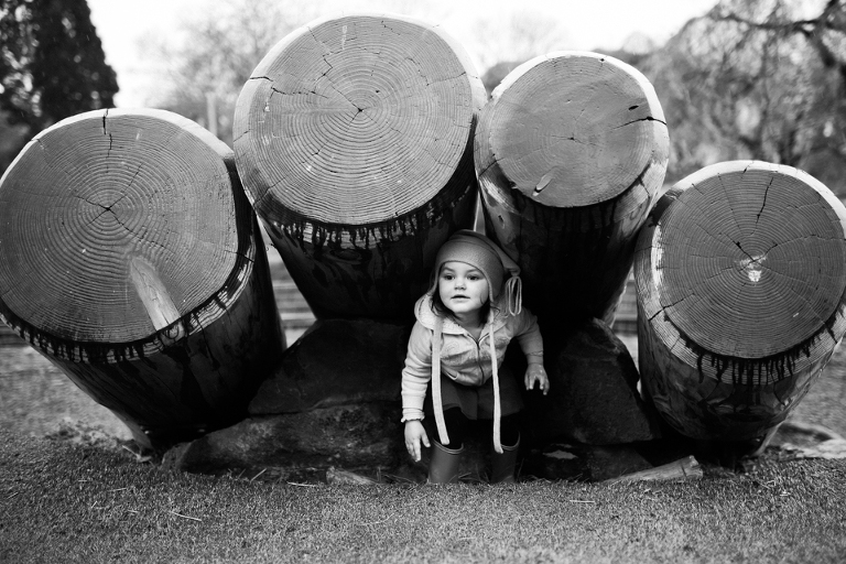 girl hiding under logs - Documentary Family Photography