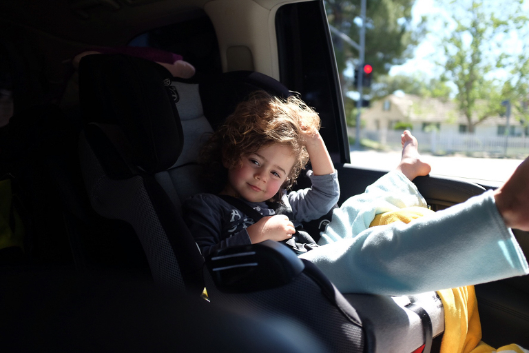 child scratches head in car seat - Documentary Family Photography
