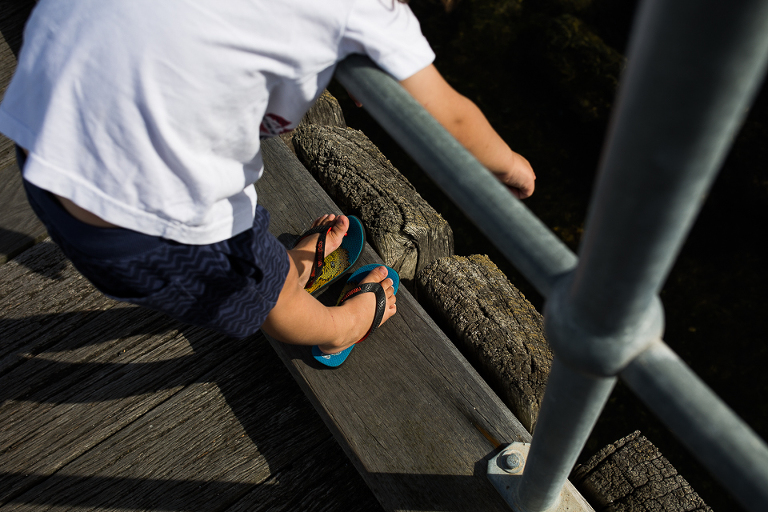 boy leans over railing - documentary family photography