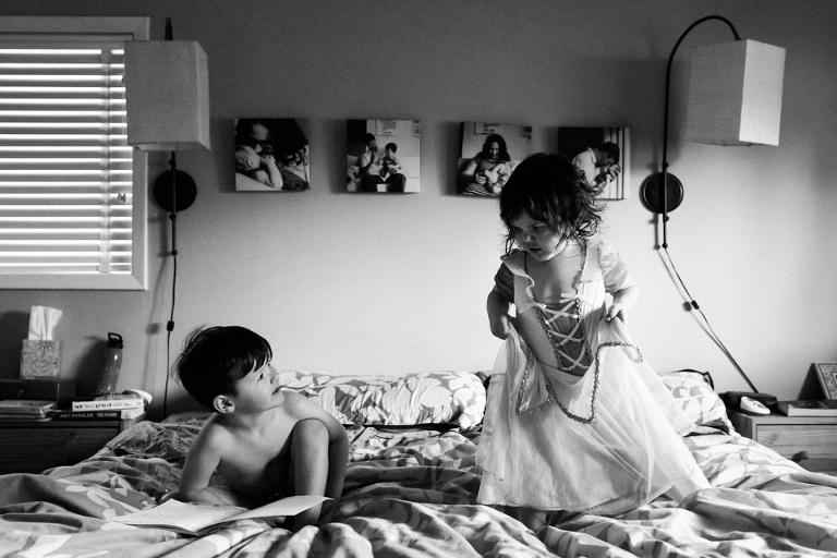 girl in costume with brother on bed - documentary family photography
