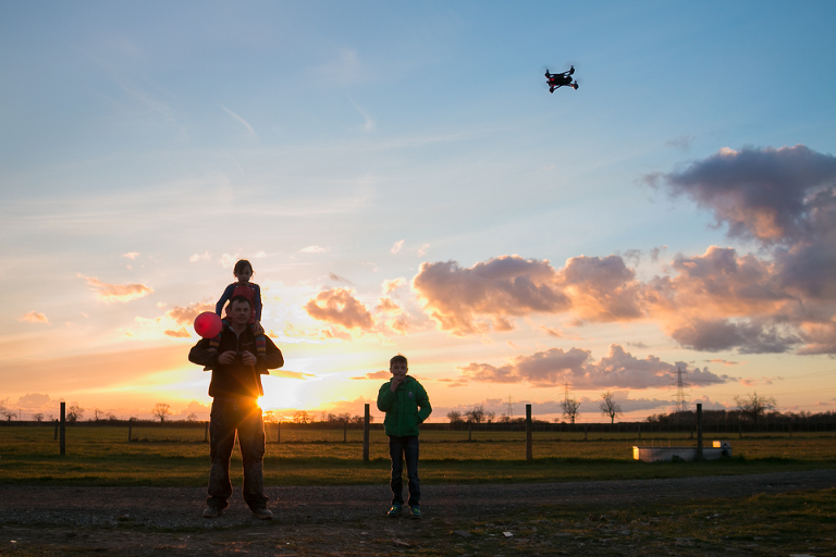 kids and father play with drone at sunset - documentary family photography