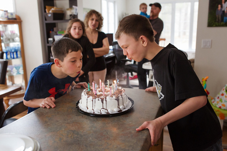 boys blow out candles on birthday cake - documentary family photography