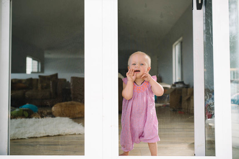 baby girl at window - documentary family photography