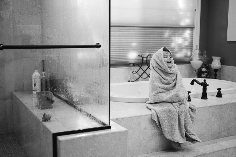 girl wrapped in towel sitting on tub edge - documentary family photography
