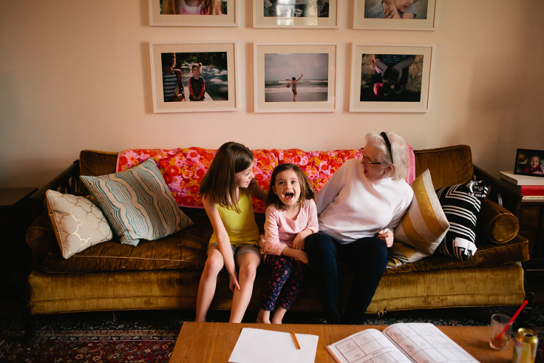 girls laugh with grandmother on couch - Documentary Family Photography