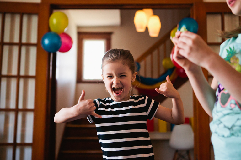 girl giving thumbs up on birthday - Documentary Family Photography