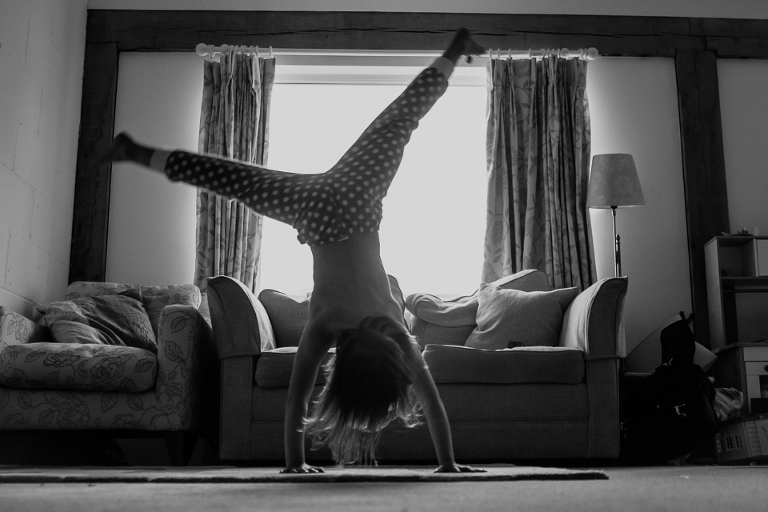 girl doing cartwheel in house - Documentary Family Photography