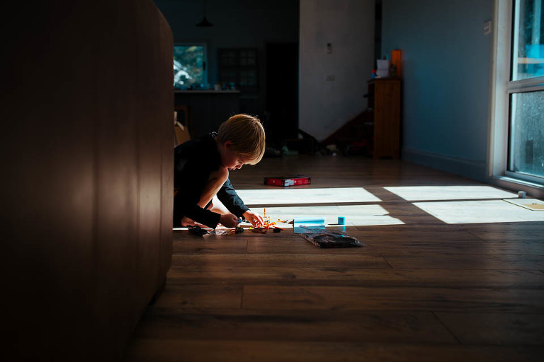 boy playing on floor in patch of sunlight - Documentary Family Photography