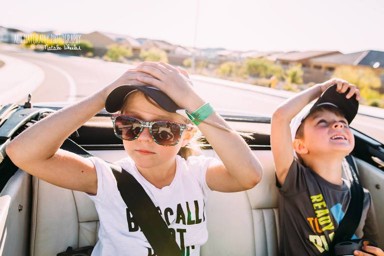 kids hold onto hats while riding in convertible - Documentary Family photography