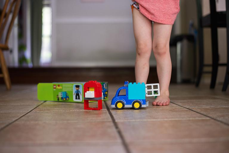 toys on floor and kid's feet - Documentary Family Photography