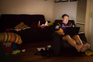 Father and son lounge with electronics - Documentary Family Photography