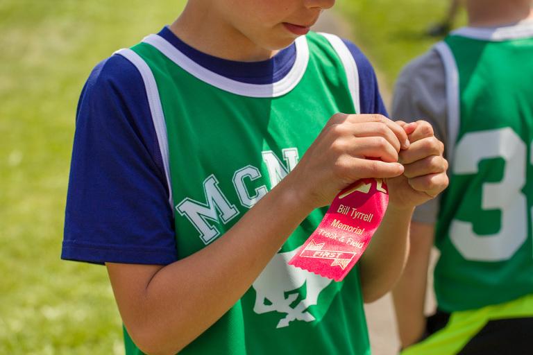 boy wins track ribbon - Documentary Family Photography