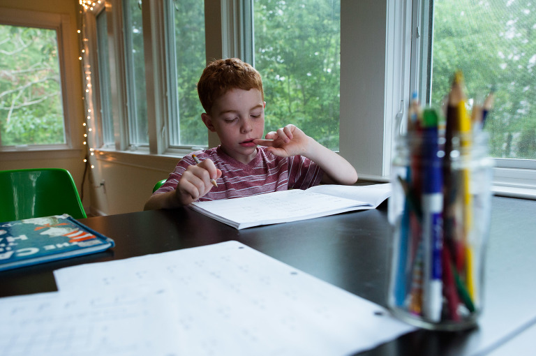 boy does schoolwork - Documentary Family PhotographyDocumentary Family Photography