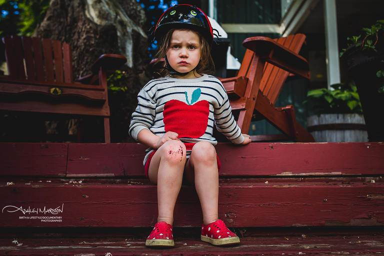 Girl sits on steps with grouchy face - Documentary Family Photography