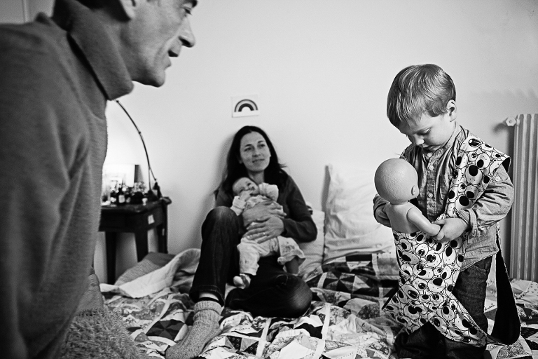 family on bed while child puts doll in carrier - documentary family photography