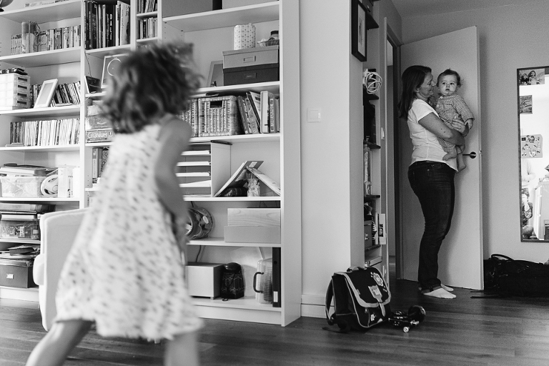 mom holds baby while girl watches on - documentary family photography