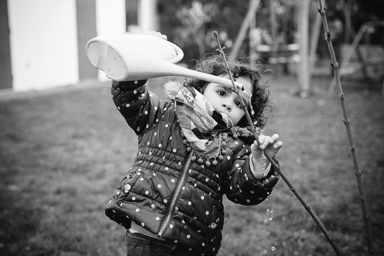 girl waters plants - documentary family photography