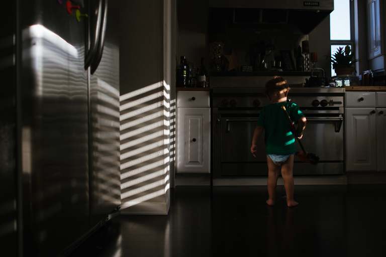 child in mini blind light - Documentary Family Photography