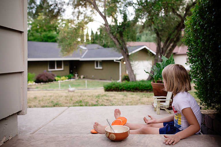 girl eats on front steps - Documentary Family Photography