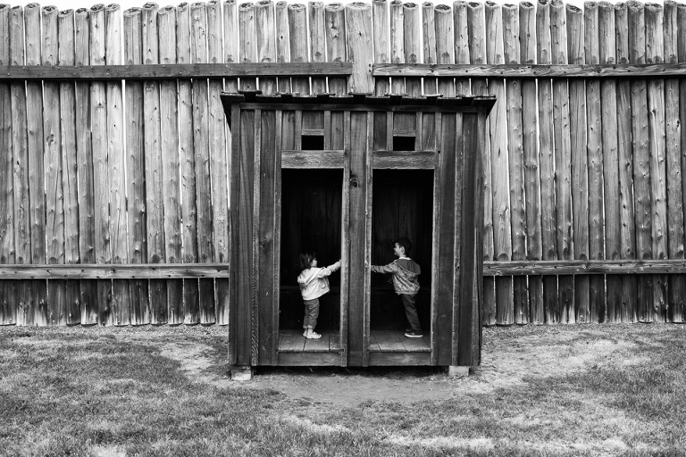 Kids in replica outhouse - Documentary Family Photography