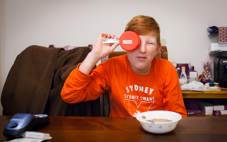 boy holding measuring cup like eyepatch - Documentary Family Photography