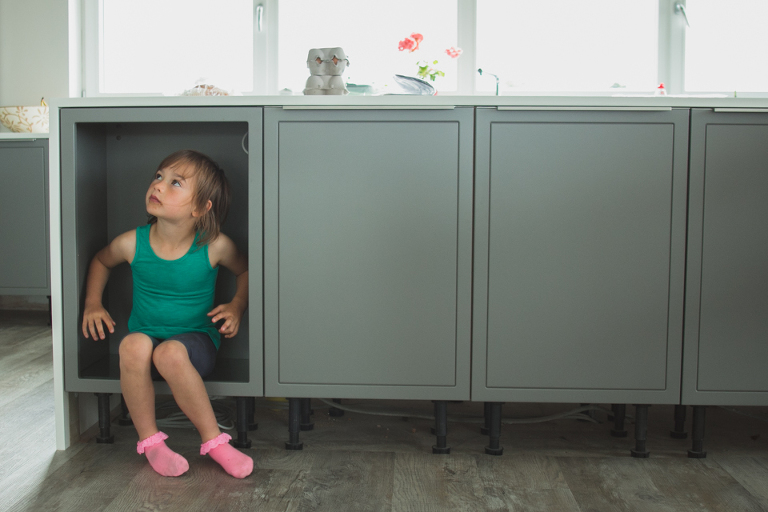 girl hiding in cabinet - Documentary Family Photography