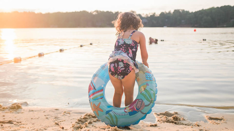 girl on beach with float toy - Documentary Family Photography