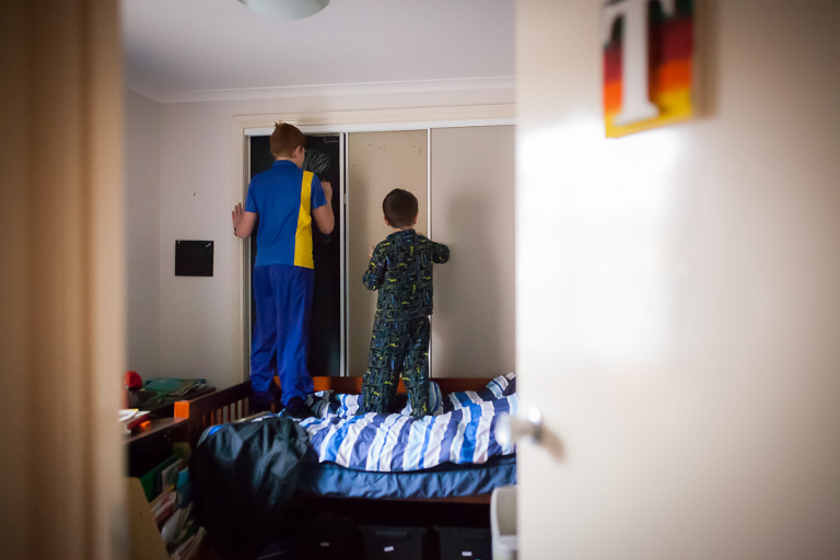kids standing on bed looking in closet - Documentary Family Photography